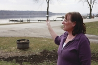 Lisa (Coborn-1979) Piatt, of LeClaire Iowa., gestures toward the Mississippi River on Sunday, March 20, 2011, as she tal